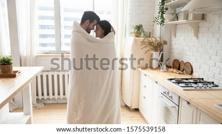 Young affectionate couple standing in modern kitchen wrapped with warm blanket, happy romantic husband and wife bonding enjoying cozy morning at home feeling love having fun covered with plaid #1575539158