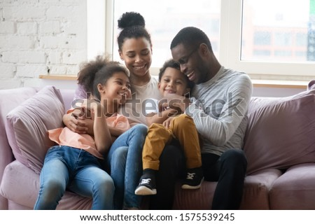 Happy african American young family with little kids sit on comfortable couch relax hug and cuddle in living room, smiling biracial parents enjoy weekend with small children, rest on sofa together #1575539245