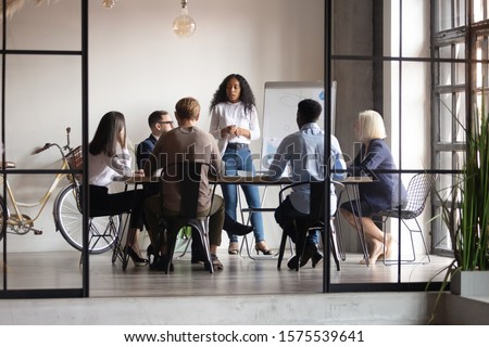 Confident african female trainer giving educational workshop to diverse team at office. Focused mixed race speaker standing near whiteboard, discussing project presentation with motivated coworkers. Royalty-Free Stock Photo #1575539641