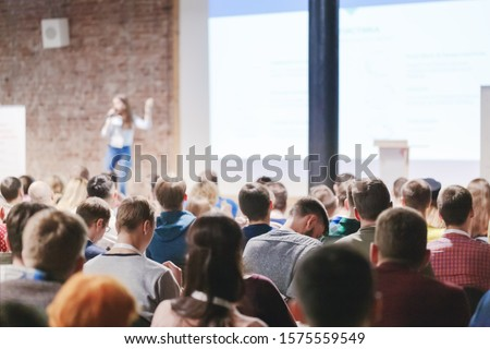Adult people at conference listen to woman speaker providing lecture on scene in big conference hall. Business and Entrepreneurship concept. Audience at the conference hall. #1575559549