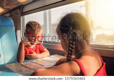 Cute little boy in sun glasses discussing vacations with his sister during their travelling by train, transport, happy family vacation and summertime, lifestyle inside portrait Royalty-Free Stock Photo #1575561463