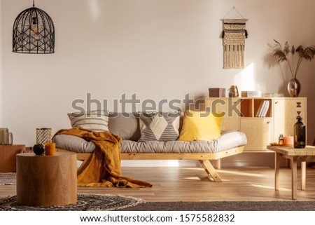 Knick knacks on wooden commode behind grey couch with pillows and blanket #1575582832