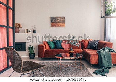 Real photo of a comfy living room interior with a round table on gray rug, wicker armchair and red corner sofa #1575588472