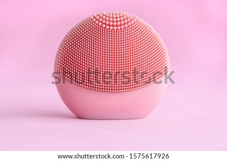 Silicone facial cleansing brushe with cleansing brush for massaging skin care on pink background. Product for face lifting, anti-aging wrinkles.