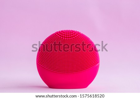 Red silicone facial cleansing brushe with cleansing brush for massaging skin care on pink background. Product for face lifting, anti-aging wrinkles.