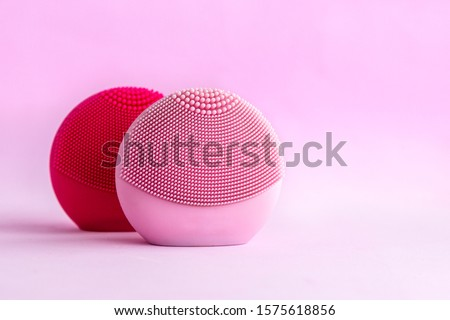 Silicone facial cleansing brushes with cleansing brush for massaging skin care on pink background. Product for face lifting, anti-aging wrinkles, copy space