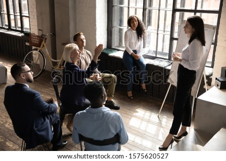 Middle aged pleasant business woman raising hand, asking questions during educational workshop at office. Multiracial people listening to confident female speaker, explaining details at meeting. #1575620527