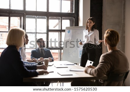 Smiling young female speaker standing near flipchart with graphs diagrams, presenting market research results to focused diverse colleagues at brainstorming meeting or educational seminar in office. #1575620530