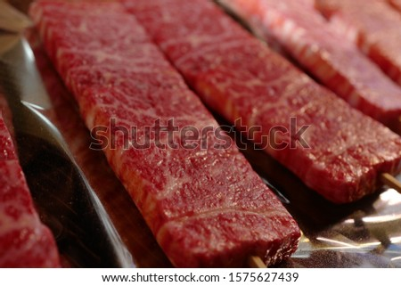 The best vibrant red juicy Japanese Kobe beef on skewers under tin foil. The blood and juiciness from the meat drips and drools down dramatically onto the tinfoil.