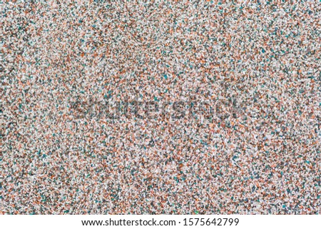 Textured background of sea colored pebbles. Abstract background of sea pebble beach. The surface of the pebble beach with pink green red white and beige pebbles photographed from above #1575642799