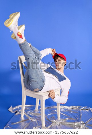 handsome fashion guy model guy posing on camera and in growth on a blue background in blue jeans and a white sweater and a red cap #1575657622