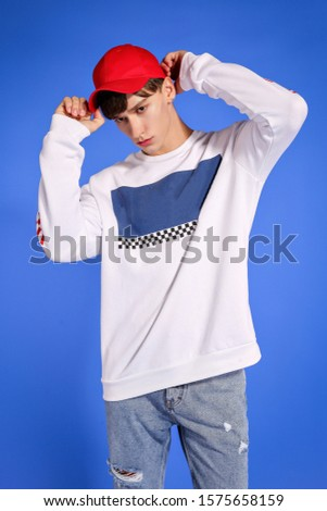 handsome fashion guy model guy posing on camera and in growth on a blue background in blue jeans and a white sweater and a red cap #1575658159