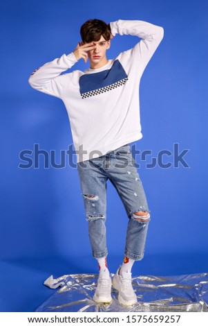 handsome fashion guy model guy posing on camera and in growth on a blue background in blue jeans and a white sweater and a red cap #1575659257