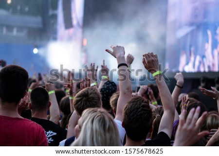 Crowd at a music concert, audience raising hands up #1575678625