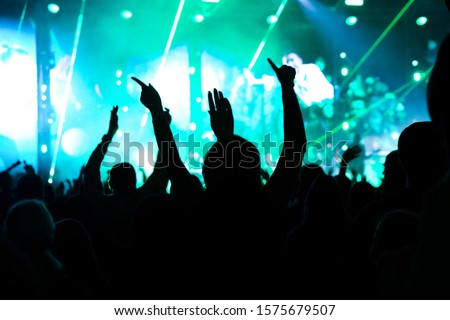 Audience with hands raised at a music festival and lights streaming down from above the stage. Soft focus, high ISO, grainy image. #1575679507