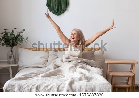 Refreshed elderly 50s female wakes up in morning stretches seated in bed in light bedroom at home, middle-aged woman feels happy and peppy after enough sleeping, greeting new day, good morning concept #1575687820