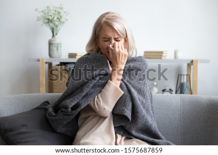 Middle-aged 50s sick frozen woman seated on sofa in living room covered with warm plaid sneezing holding paper napkin blow out runny nose feels unhealthy, seasonal cold, weakened immune system concept #1575687859