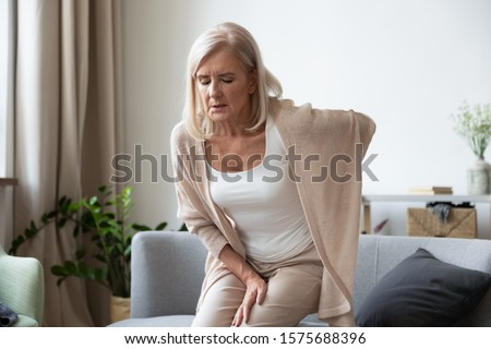 Elderly 60s woman got up from couch felt severe painful feelings in lumbar, massaging low back to reduce ache, suffer from backache discomfort, diseases of older people, sciatic nerve injury concept Royalty-Free Stock Photo #1575688396