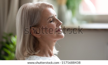 Close up side view 50s blonde woman closed eyes feels calm and serene enjoy free time at home, life without stress, good healthy habit at retired life practises of breathing techniques do yoga concept Royalty-Free Stock Photo #1575688438