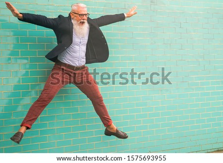 Crazy man jumping. Happy male celebrating. Energetic happy mature man  in casual clothes jumping, wall isolated in light green background - Joyful elderly lifestyle concept - Focus on the face.