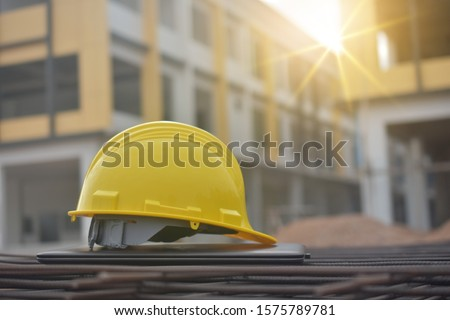 Hard hat safety on computer notebook building construction estate background