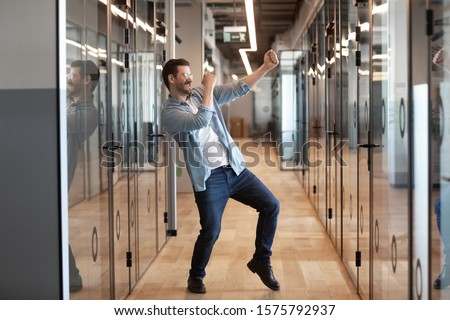 In office hallway dancing happy worker got promotion celebrating success higher rate of pay receive financial bonus, candidate for post was hired, employee feels excited work done, its Friday concept #1575792937