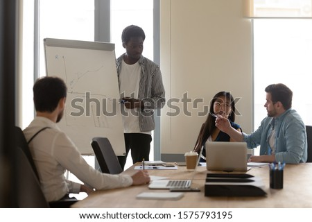 Corporate training process concept company employees improving skills gain new knowledge listen coach, client ask question about info shown on flip chart analyzing together graphs financial statistics #1575793195