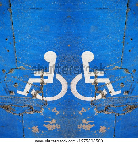 traditional universal icon for disabled access and parking zone white on blue painted surface #1575806500