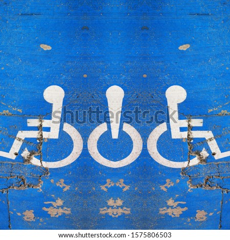 traditional universal icon for disabled access and parking zone white on blue painted surface #1575806503