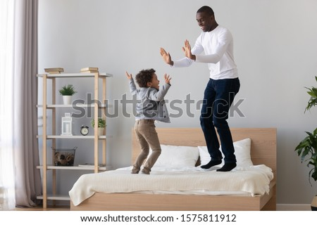 Joyful african american young man jumping on bed, clapping hands with cute little laughing preschool son. Small happy mixed race boy spending active weekend leisure time, having fun with smiling dad. #1575811912
