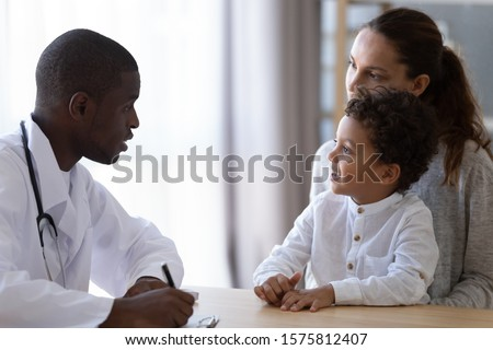 Young african american pediatrician listening to little mixed race preschool patient complaints, taking down notes. Small kid boy sitting on smiling mothers knees, talking with focused kind doctor. #1575812407