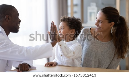 Happy african american young male doctor giving high five to smiling mixed race little kid boy, celebrating good result of prescribed medical treatment or welcoming new patient with mum at clinic. #1575812413