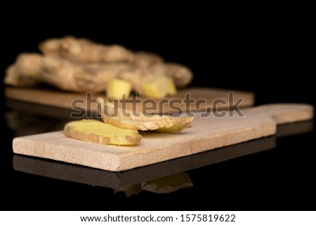 Group of two whole two slices two pieces of fresh brown ginger on wooden cutting board on bamboo cutting board isolated on black glass #1575819622