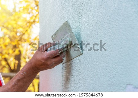 Application Of Facade Plaster,Worker Plastering The Facade Of The Building, Close-Up. Royalty-Free Stock Photo #1575844678