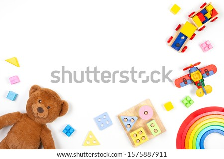 Baby kids toys background. Teddy bear, wooden educational stacking color recognition puzzle toy, wooden train, teddy bear and colorful blocks on white background. Top view, flat lay #1575887911
