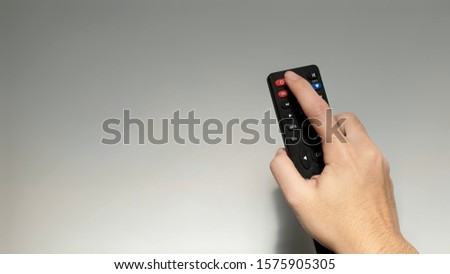 Hand with multimedia tv remote control. #1575905305