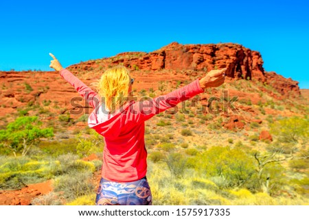Finke Gorge National Park, Northern Territory, Australia Outback. Carefree woman looking panorama from Kalaranga Lookout with spectacular views of sandstone amphitheatre surrounded by rugged scenery. Royalty-Free Stock Photo #1575917335