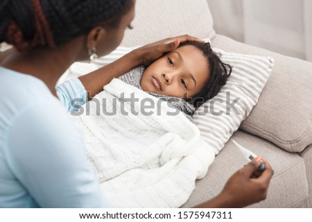 Fever Concept. Sick child in bed, mother holding thermometer, comforting poor girl Royalty-Free Stock Photo #1575947311