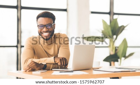 Confident Businessman. Happy african guy smiling at camera working at office. Panorama, free space #1575962707