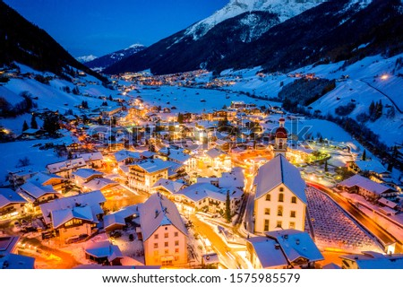 Winter night cityscape in the Austrian town of Neustift. Aerial view of the town center and the church. Night illumination of houses and traffic light. Tyrol, Stubai Valley #1575985579