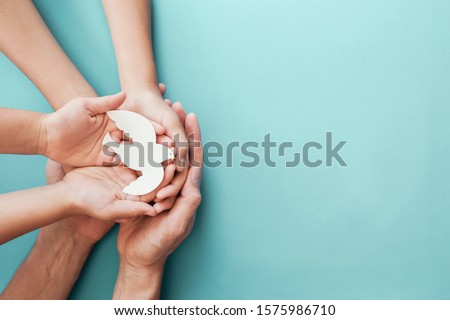Adult and child hands holding white dove bird on blue background, international day of peace or world peace day concept, sustainable consumption, csr responsible business, animal rights, hope concept #1575986710