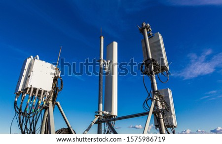 Telecommunication masts with microwave, radio panel antennas, outdoor remote radio units, power cables, coaxial cables, optic fibers are installed on the top mast and blue sky as background. #1575986719