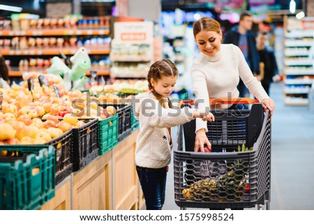 Family in the supermarket. Beautiful young mom and her little daughter smiling and buying food. The concept of healthy eating. Harvest #1575998524