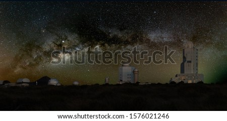 Astronomical Observatory under the bright stars. Milky Way galaxy on the dark mountain sky. Towers and domes of huge telescopes are aimed at celestial bodies. #1576021246