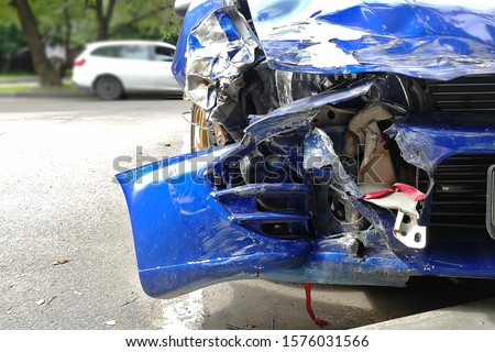 Close-up of a blue totally wrecked car on a street in a parking lot. destroyed bumper, headlight, hood, fender. front view. In the background a white car in blur. #1576031566