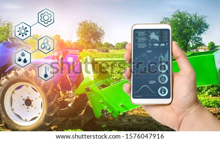 Farmer holds smartphone with infographic on tractor background with potato digger. Farming and smart agriculture. Agricultural machinery, data analyzing on plants status. Harvesting. #1576047916