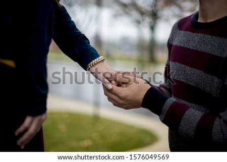 A closeup shot of male proposing to his girlfriend with a blurred background #1576049569