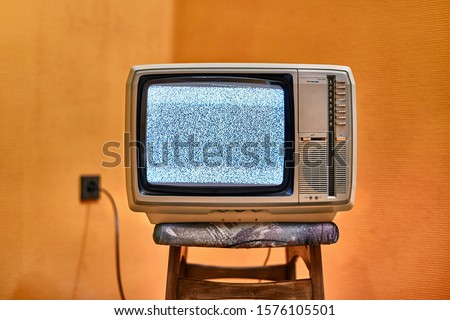 Vintage TV set on a chair in an empty room #1576105501