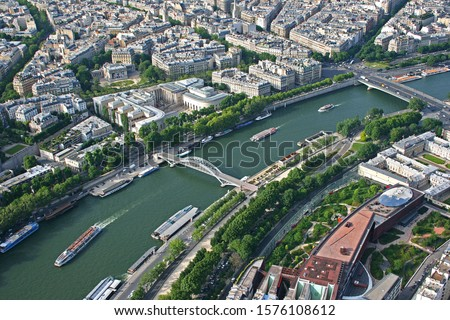 Paris. A view from the Eiffel Tower of the River Seine.Two bridges can be seen. The nearer one is a footbridge called the Parrerelle Debilly, a through arch bridge. The other bridge is the Alma Bridge #1576108612