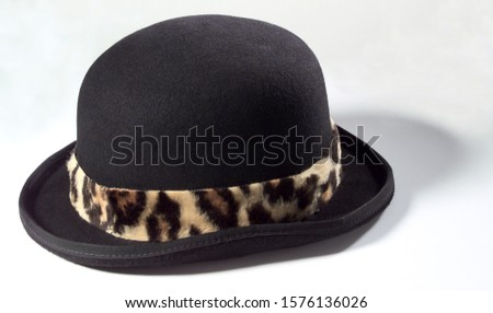 A photograph of a bowler hat with an imitation leopard strap #1576136026